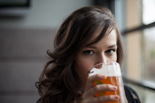 Young Woman Drinking a Pint Glass of Pale Ale